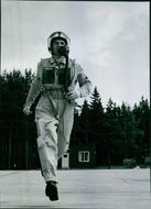 A fighter pilot running, wearing mask and suit.