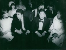 """Alexandre """"Sacha"""" Distel and Johnny Hallyday with women, sitting."""