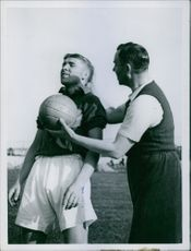Man giving football to another man forcefully.