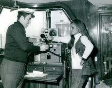 The Captain of the ship handing over the bridge phone to Dalida.