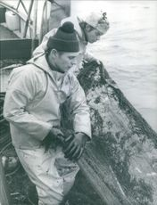 A photo of two fishermen with a net.