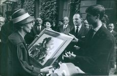 A group of people are presenting a picture frame to Queen consort of Sweden Louise Mountbatten