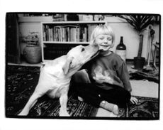 A little boy is enjoying the attention and love of his pet.
