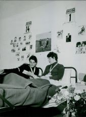 Marielle Goitschel and Christine Goitsche lying on bed and communicating with each other, 1964.