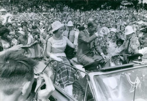Queen Elizabeth II and Prince Philip, Duke of Edinburgh, waves to the cheering crowd during their parade. 1963.