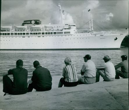 PEOPLE ARE SITTING NEAR A RIVER & LOOKING aT A BIG SHIP