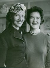 Queen Anne-Marie posing with another woman, facing towards camera and smiling.