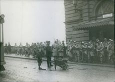 French troops standing beside the road, while a cleaner standing with carriage in Germany.