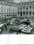 A view of building, people walking in the car park. 1968