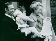 A royal photo of Prince Michael of Kent carrying his son Lord Frederick and Princess Michael of Kent holding their second baby Lady Gabriella Marina Alexandra Ophelia.