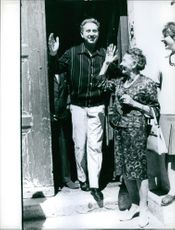 Charles Trenet and an old woman smiling and waving their hands to greet the people.