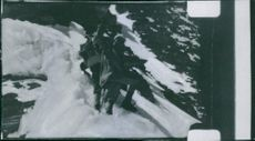 Mountain climbers travelling down the snowy slope.