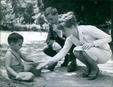 Russian movie stars in Paris with a boy playing on the sand, 1960.