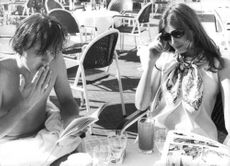 David Hemmings sitting at table with a woman.