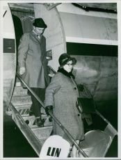 Man and woman getting off from the airplane.