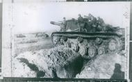 Soldiers in a rocky field wind heavy tank and weapon, 1959.