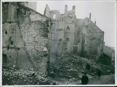 View of ruined buildings in street, people passing by.