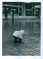 A child playing in water on road.