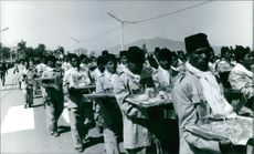 People in the street holding food during the wedding of King Birendra and Queen Aishwarya of Nepal, 1970.