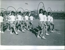 Young ladies each holding a hula-hoop on their backs, making a halo on their heads while parading in Iran.