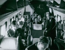 Pierre Mendes France with men and woman in an airplane