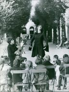 Women acting and singing in front of the children while the other boy playing guitarist