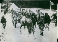 Villagers people walking behind cart. On the flight over mountains during WWI 1914-18