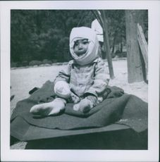 A cute little child with a cloth wrapped around the sides of his face, sitting and looking at the camera.