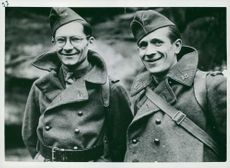 Two soldiers smiling on camera.