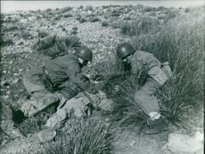 Two soldiers helping the third one lying on the ground.