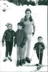 Farah Pahlavi with her three children at that time on snowy hills.