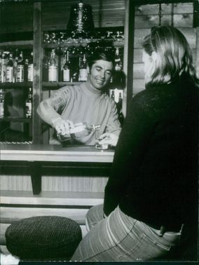 Karl Schranz pouring drinks to another man. 1969.