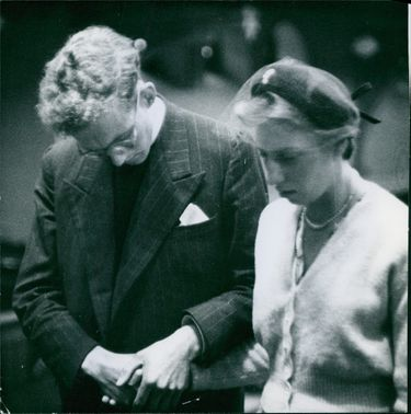 Man holding woman's hand and praying. 1954