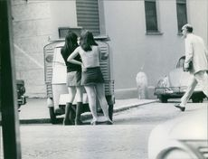 Women standing together beside a vehicle and looking, while a man passing.