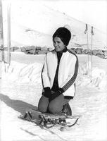 Farah Pahlavi sitting on sleigh.