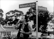 A man eats a burger outside McDonald's restaurant on McDonald's own street, McDonald's-Straße