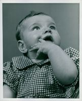 Vintage photo of a baby looking up curiously, her hand resting on her chin.