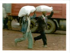Rwanda war:two rwandan refugees run their two sacks of a flour kimbumba.
