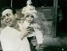 Man smiling while holding a baby in Nepal, 1970.