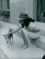 Jacqueline Boyer siting with a dog and pampering.