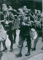 English soldiers marching. One of them is playing an accordion to lighten the burden of the march.