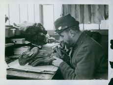 Soldier doing something in the table during Tyskland war, 1914.