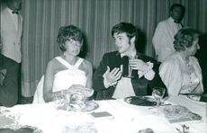 Robert Hossein drinking and talking to a woman.