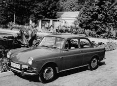 A Volkswagen car parked in front of the garden area.