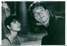 Patrick Swayze and Demi Moore sitting together and looking up in one of the scenes in film Ghost.