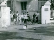 People standing at the entrance gate looking at gas grenade on the street in Vietnam, 1966.