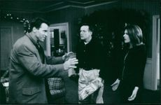 A photo of the film Jingle All the Way starring  Arnold Schwarzenegger, Rita Wilson and Phil Hartman. 1996