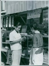Man and woman standing outside of the shop, holding something in his hands and looking at it.