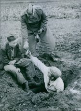 Men precipitate a bomb, by digging and disposing into it. 1943