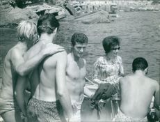 Soraya Esfandiary Bakhtiari with other few men beside a seashore. Men taking bath in the water.